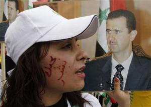 A supporter of Syrian President Bashar al-Assad carrying his image, with words written on her face that reads in Arabic ''Bashar I love you'', takes part in a rally to commemorate the 65th anniversary of the foundation of the Baath Party, at al-Sabaa Bahrat square in Damascus April 7, 2012. Credit: Reuters/Khaled al-Hariri
