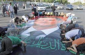 "supporters of the ""secular"" Assad bow down to kiss his mega poster."