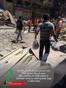 Des volontaires de JAFRA distribuent des sacs de nourriture.