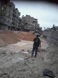 A Jafra volonteer looks at piles of debris during a cleaning campaign