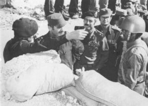 Hafez al-Assad (second from left) is briefed by one of his officers in a reserve trench. Next to Hafez al-Assad is Defense Minister Mustafa Tlas, and next to Tlas is Rifaat al-Assad, 1973.