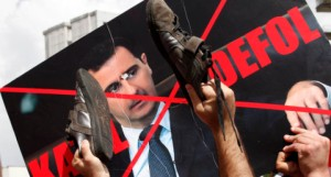 "Protesters use their shoes to hit a defaced poster of Syria's President Bashar Al-Assad during a demonstration to express solidarity with Syria's anti-government protesters in front of the Syrian embassy in Ankara June 10, 2011. The words on the poster read: ""Murderer. Go away"". REUTERS/Umit Bektas (TURKEY - Tags: POLITICS CIVIL UNREST IMAGES OF THE DAY)"